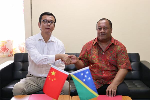 Yao Ming Deputy Head of People's Republic of China Embassy in SI shaking hands with Heatlh Minister Dickson Mua following the signing of the hand over certificate.