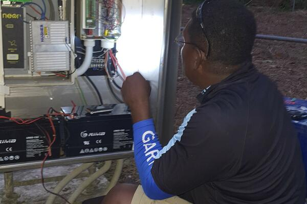 MET Service Chief Technical  Officer, Mr. Barnabas Tahunipue at work on the Automatic Weather Station in Tikopia