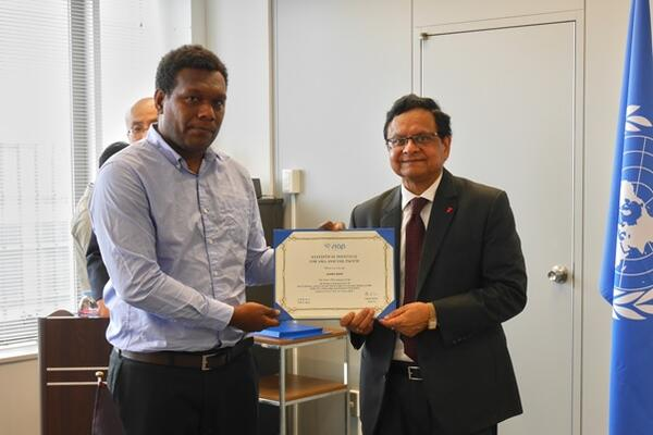 Graeme Risoni receives his certificate of completion from the UN SIAP Director, Ashish Kumar.