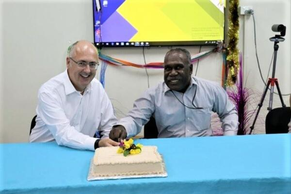 Dr Lachlan Strahan and Auditor General Peter Lokay celebrate by cutting a cake.