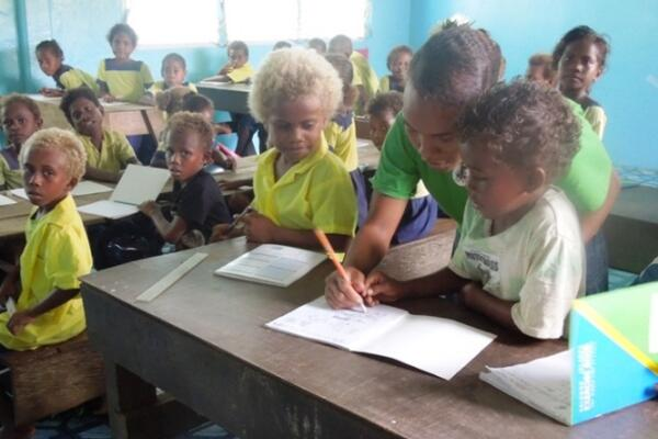 Little children of the Kilusakwalo Christian Community High School in their newly renovated classroom, thanks to their dedicated teachers and Jane Sheils, an Australian Volunteer.