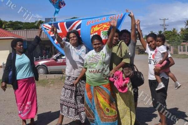 Semo villagers in Fiji on the roadside waiting to meet the country's rugby champs.
