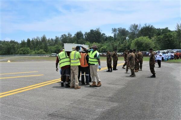 Casket being sprayed at Momote airport before being released.