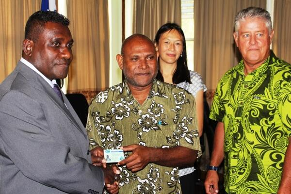 Prime Minister Gordon Darcy Lilo receiving his new licence from Deputy Principal Licensing Officer, George Tapo, accompanied by Acting New Zealand High Commissioner, Sarah Wong(back) and Commissioner of Inland Revenue, Mark Bell (right)