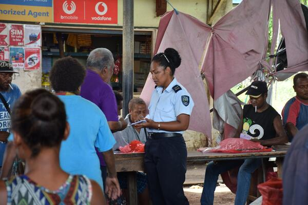 PC Luciana Binuika  explaining the police awareness pamphlets to an elder at Kukukm Market.
