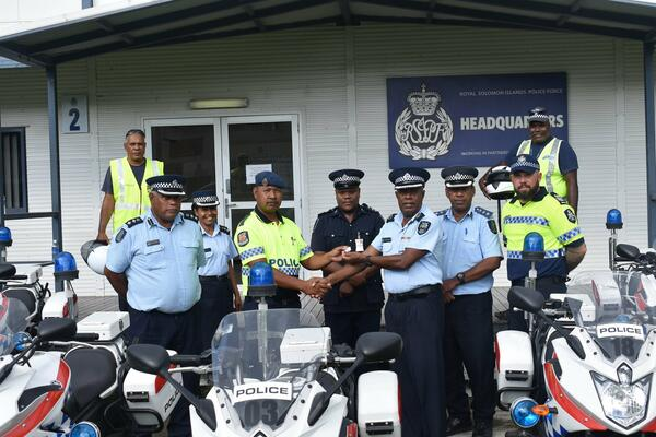 Constable Helai of the RPNGC hands over the keys of the gifted motorcycles to Acting DC Operation Joseph Manelugu.
