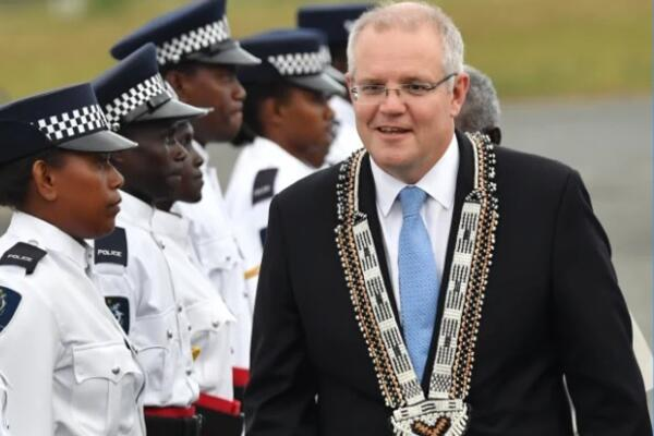 Australian Prime Minister Scott Morrison inspects a guard of honour by the Royal Solomon Islands Police Force after arriving at Honiara International Airport yesterday.