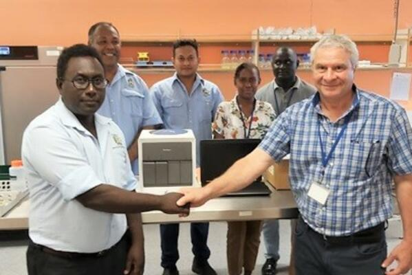 Front – MHMS Dr Gregory Jilini receiving the GeneXpert Machine and the laptop from WHO, Dr. Magdi Kassem with a handshake. Witnessing the handover were the Director of National Public Health laboratory, Mr. Dickson Manongi, Mr. Oliver Lukos (Medical Lab Technologist) and WHO staff; Ms Lanique Pitasua and Mr. Robinson Minevaleke at the back.