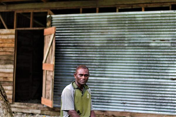 Charles Wesley Daveta from Lale village, Ranongga Island, in the Western Province, sits in front of his cocoa shed.