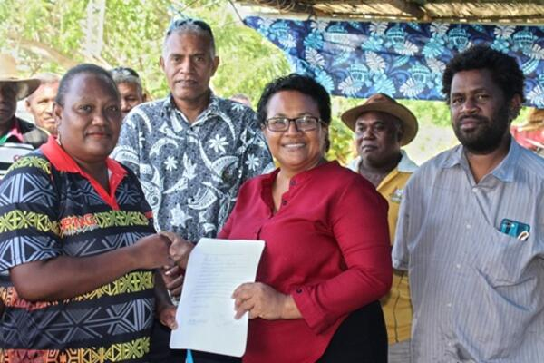 Wendy Saki Besa'a, a cassava out-grower got her signed agreement from MAL PS, Ethel Francis as Sape Farm Managing Director, Dr. Paul Bosawai Popora (right) and Undersecretary Technical Michael Ho'ota (from back row) looks on.