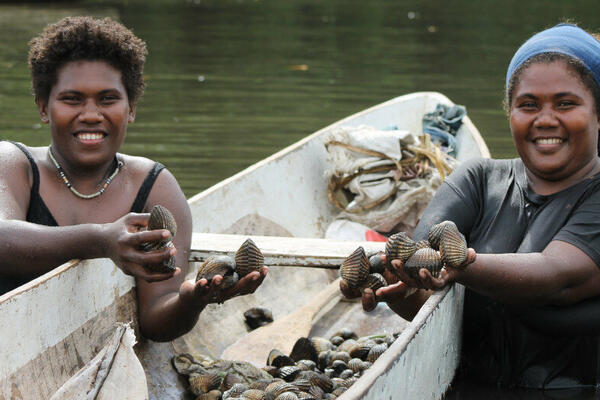 Women from Solomon Islands smile as they hold up clams. A new study says that well-being of South Pacific islanders remained steady despite the drop in tourism.