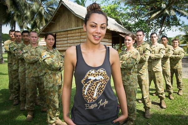 Ms. Prinnie Stevens flanked by Aussie troops in Honiara, Solomon Islands.