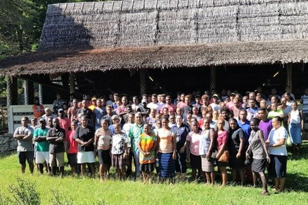MFAET PS Mr Collin Beck and Second Secretary Christina Skoumbourdis from the Australian High Commission in a photo shoot together with the workers after the Pre-departure briefing at St. Barnabas Leaf hut.