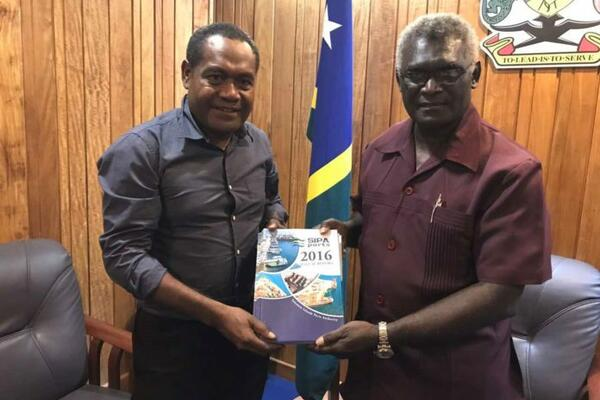 Chairman of SIPA Board, Mr Titiulu, left, handing over the Annual Reports for years 2011 - 2016 to Prime Minister Sogavare.