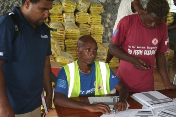 AusAID's rapid response officer, Eric Lui (L) and local authorities working out food distribution in Temotu Province.
