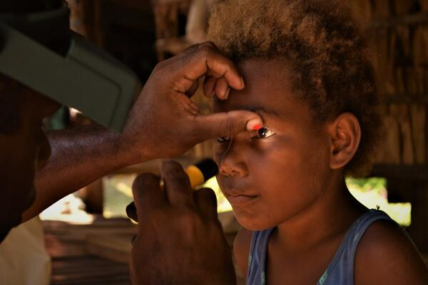 A trachoma grader examine the eyes of a young girl in Solomon Islands.