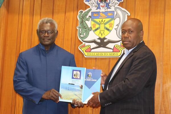 Minister for Police, National Security and Correctional Services Hon. Anthony Veke hands over the security strategy documents to the Prime Minister.