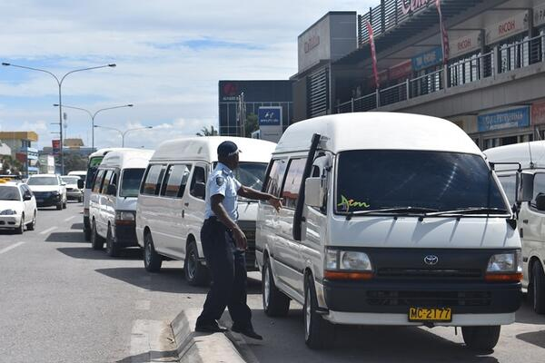 RSIPF traffic officers controlling traffic including buses at the Honiara Central Market bus stop.