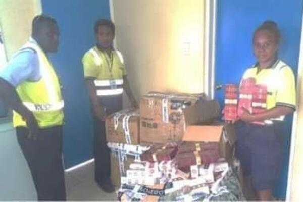 Customs Officers with the seized cigarettes.