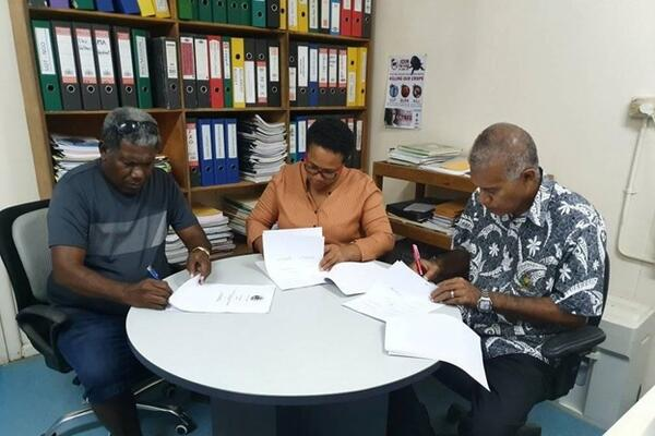 Mr Tony Tepeaihana, Managing Director of Food Works Supplies Ltd, MAL Permanent Secretary Mrs Ethel Tebengi Frances and MAL Undersecretary Technical Michael Ho'ota signing the funding agreement.