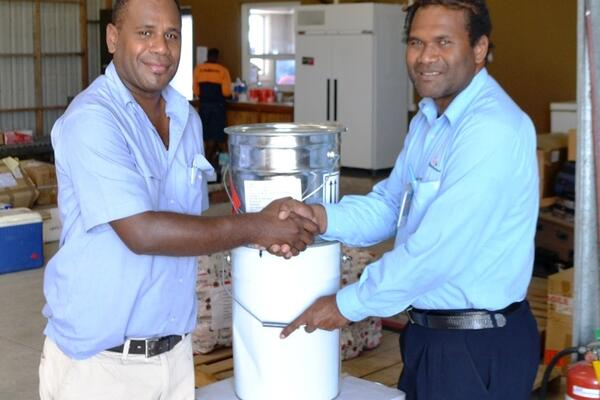 The buckets of paint were handed over to the President of the Rotary Club Sebastian Ilala (left).
