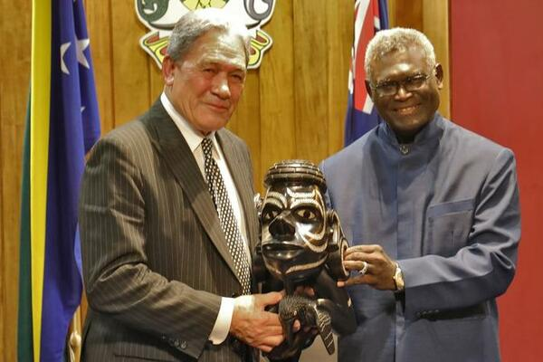 Solomon Islands Prime Minister Manasseh Sogavare presents a Nguzu Nguzu to New Zealand's Deputy Prime Minister Winston Peters.