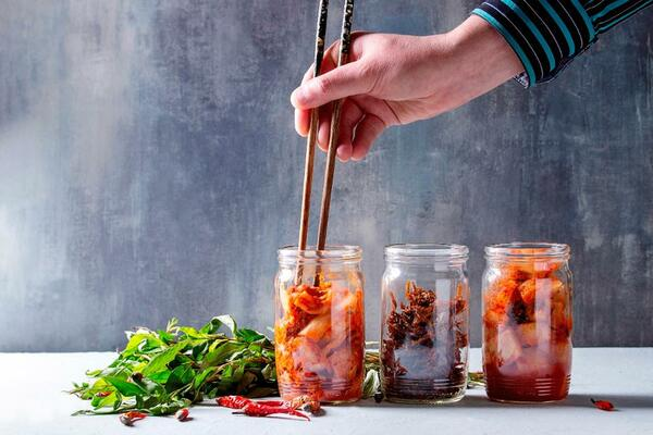 Korean traditional fermented appetizer kimchi cabbage and radish salad, fish snack served in glass jars.