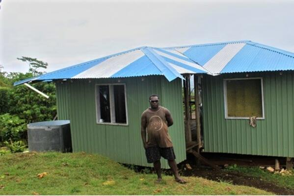 Eddie Voko in-front of his new permanent home that he build through money acquired from shallot sales. The home is in construction phase and is nearing completion.