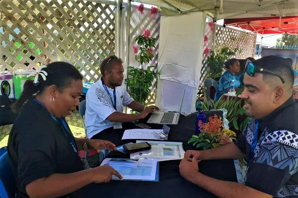 Strongim Bisnis Senior Business Advisor James McGoon at a booth talking with one of the 28 tourism operators.