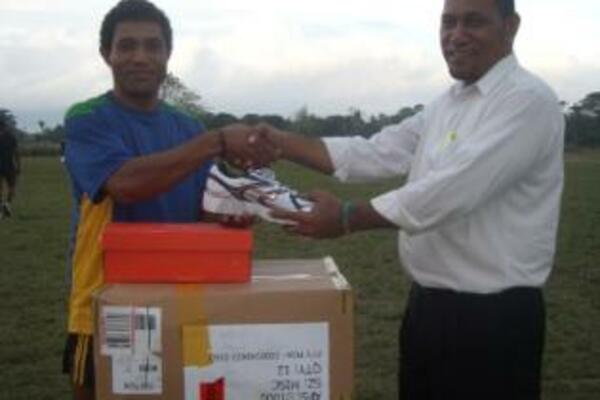 Rugby 7s coach Jim Seuika (r) handing over the sporting equipment to the 7s captain Edmond Tay.