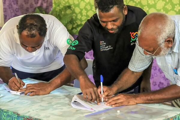 The signing of the partnership between Kastom Garden Association (KGA) and Oxfam is part of the Australian Humanitarian Partnership (AHP) COVID-19 response. Pictured are Oxfam Solomon Islands Country Coordinator Richard Sakiri (left), Oxfam Humanitarian Coordinator Nicholas Suava (centre) and KGA Chairman Frank Tabai.