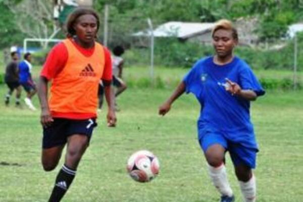 Rose Gwali (L) competes with Joy Timo of Honiara Select for the ball.