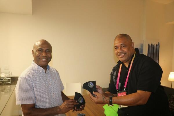 Commissioner General Ambassador, Moses Kouni Mose and Communications Volunteer, Mr. Kelepi Abariga display customized Solomon Islands face masks at the Solomon Islands Pavilion.