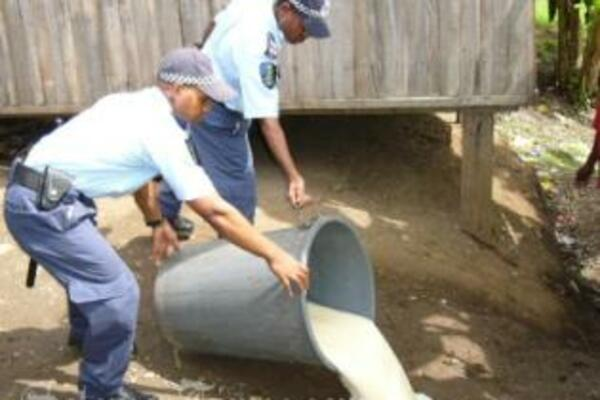 Police pouring out litres of home brewed Kwaso destined for the streets of Honiara.