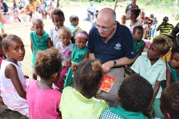 Australian High Commissioner Dr Lachlan Strahan reads gifted books to children at Papagu Early Childhood Development Centre.