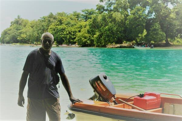 Jesse standing beside his ray boat, behind him is Taro Island the capital of Choiseul Province.