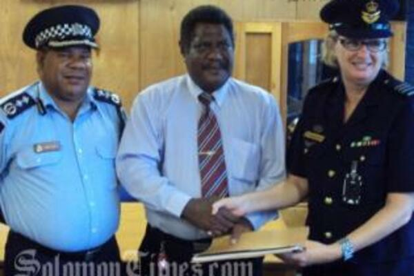 Acting Police Commissioner, Walter Kola, Hon. James Tora and Wing Commander, Wendy Horder handing over the letter of arrangements.