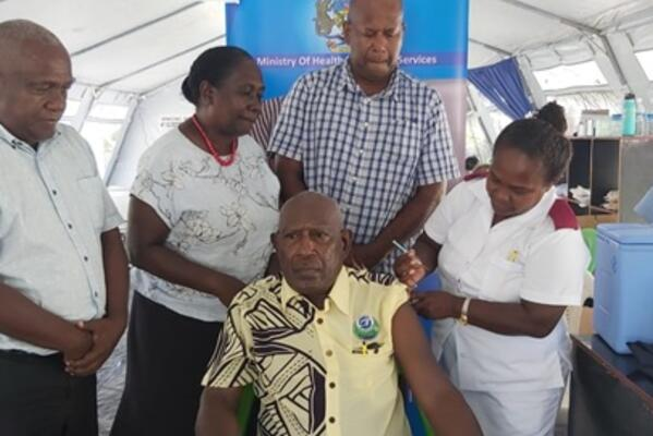 Supervising Premier Hon. Isaac Tatapu ready to receive his vaccination with which was witnessed by (back row from left) MHMS Director Planning Mr. Ivan Ghemu, Health PS Mrs Pauline McNeil and Western Provincial Health Director Dr Dickson Boara.